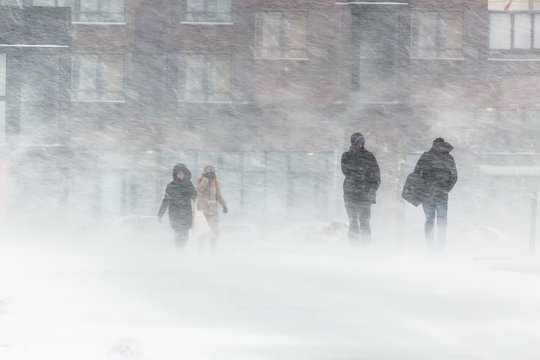 The blizzard, strong wind, sleet, against the background of houses blurred silhouettes of people, they try to hide from bad weather, overcome all difficulties of severe climate. go to the bus stop