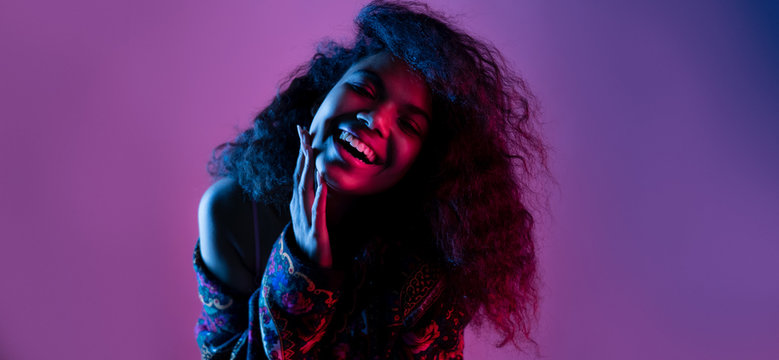 Happy smiling fashion young african girl black woman wear stylish jacket looking at camera laughing isolated on party disco purple studio background, banner for website design, portrait, copy space