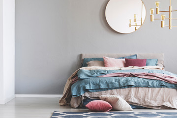 Chick round mirror on grey empty copy space wall in elegant bedroom interior with warm bed with blue, pastel pink and beige bedding