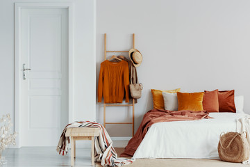 Sweaters, wicker hat and bag on wooden ladder next to king size bed with velvet pillows in white bedroom interior, copy space on empty wall