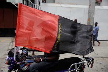 A protester rides a motorbike as he carries a flag during a march called by opposition parties and civil society groups to protest against the government of President Jovenel Moise in Port-au-Prince