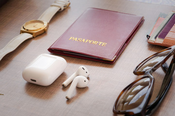 life style flat lay white air pods, passport, gold watch, brown sunglasses