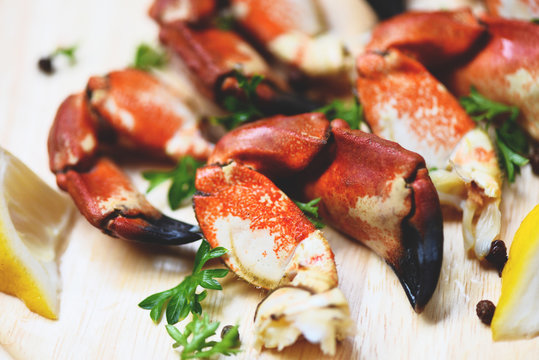Cooked crabs boiled on wooden board with lemon on plate served seafood - Red stone crab claw