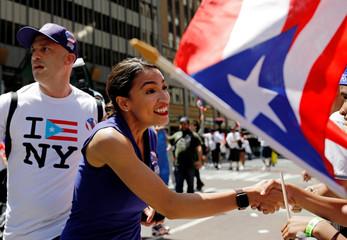 Representative Alexandria Ocasio-Cortez shakes hands on 5th Avenue at the annual Puerto Rican Day Parade.