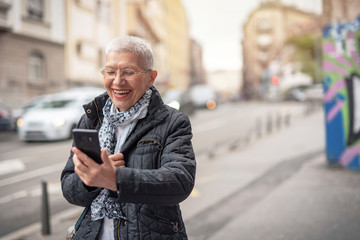 Happy senior old woman talking on her cell phone in the street