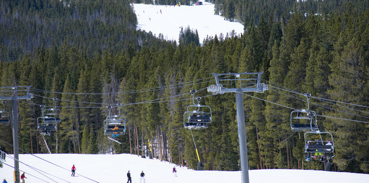 Skiers riding up a ski lift - Multi-chair lift in Denver