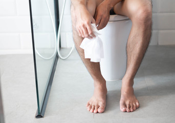 Closeup man sitting on toilet with tissue paper in hand, selective focus
