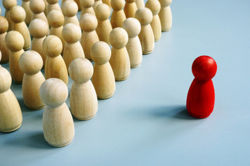 Successful leader of team as red figurine out of the crowd.