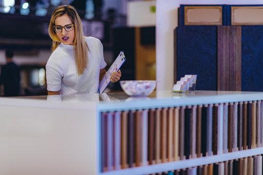 Female decorator choosing materials in home design showroom