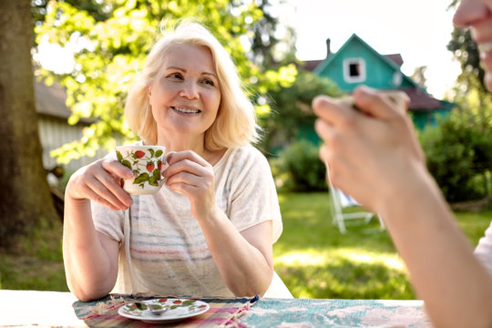Blonde beautiful grandmother relaxing with her family at the garden on sunny summer day.