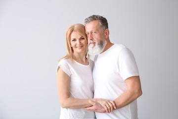 Beautiful elderly couple on light background