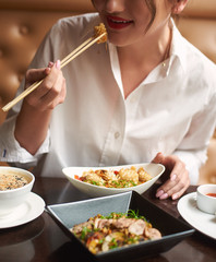 Crop of pretty woman in white blouse with red lips ordering meal in luxury Japanese restaurant. Lady eating four course lunch including soup, tempura shrimps, noodles and warm salad.