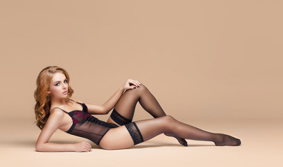 Fashion model posing in erotic underwear. Woman in beautiful black lingerie over colored background.