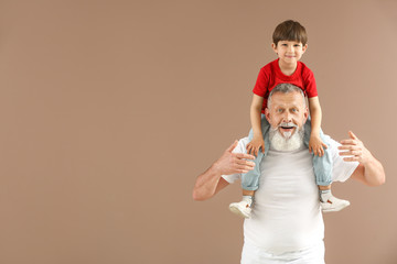 Funny little boy with grandfather on color background