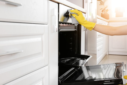 Woman cleaning oven at home