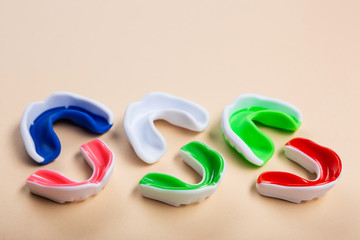 mouth guards for boxing or karate lie on a beige background, three large mouth guards and three small mouth guards, the concept of sport