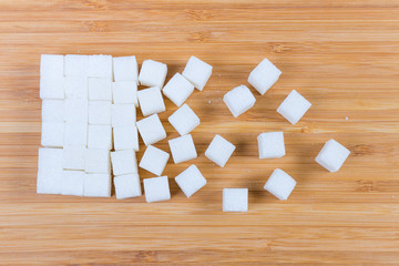 Top view of white sugar cubes on a wooden surface