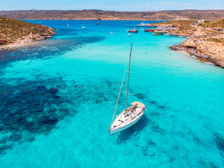 Obraz Concept paradise vacation. White yacht with sail in clear water of sea with sand. Blue Lagoon Comino Malta. Aerial view - fototapety do salonu
