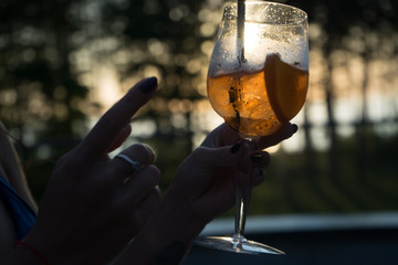 A girl holds a glass with a cocktail. The picture was taken in the spa center by the pool, against the backdrop of the sunset.