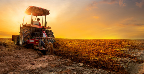 tractor is preparing the soil for planting over sunset sky background Papier Peint