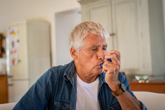 Senior man using asthma pump