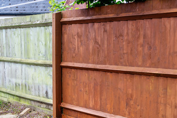 Painting old wooden fence with a brown paint, renovation concept, before and after image Wall mural