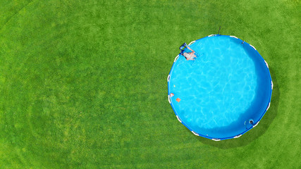 Aerial. Metal frame pool with water on a green grass lawn. Top view. Copy space.