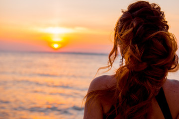 woman at sunset. girl at sunset. Girl on background setting sun. Woman watching the sunset. Girl in black dress with evening hairstyle. romantic date in the evening. Luxury woman on the beach.