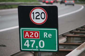 Distance sign at motorway A20 heading gouda with attention sign for speed in kilometers