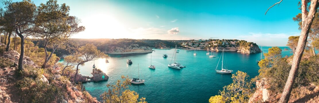 Panorama view of a beach bay with turquoise blue water and sailing boats and yachts at anchor with framed pine trees. Lovely romantic Cala Portals Vells, Mallorca, Spain. Balearic Islands