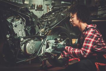 African american woman mechanic repairing a motorcycle in a workshop
