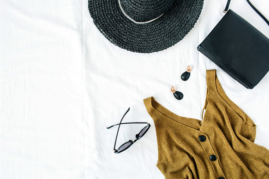 Feminine fashion composition with hat, blouse, earrings, purse, sunglasses on white background. Flat lay, top view minimalist stylish trendy elegant clothes hero header.