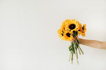 Women's hand hold yellow sunflowers bouquet on white background. Summer floral concept. Fototapete