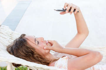 Beautiful teen girl takes a selfie on the phone lying in a hammock