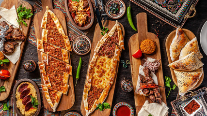 Traditional Turkish cuisine. Pizza, pita, pidesi, sucuk, hummus, kebab, bulgar. Many dishes on the table. Serving dishes in restaurant. Background image. Top view, flat lay