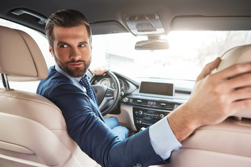 Careful driving. Successful young bearded businessman in formal wear is driving to a business meeting Wall mural
