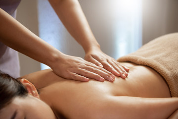 Masseuse doing massage on Asian female body in the spa salon.