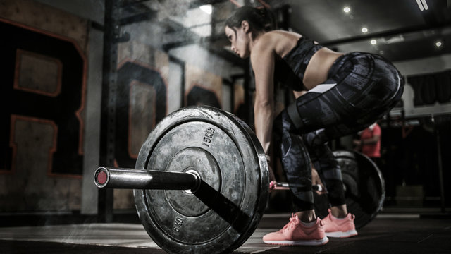 Sport. Muscular women lifting deadlift in the gym with barbell. Dramatic interior with smoke.