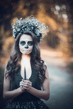 Closeup portrait of Calavera Catrina in black dress. Sugar skull makeup. Dia de los muertos. Day of The Dead. Halloween