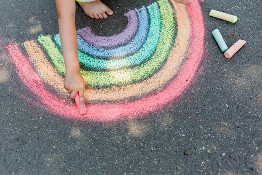 child's drawing of rainbow and colorful chalks on a street