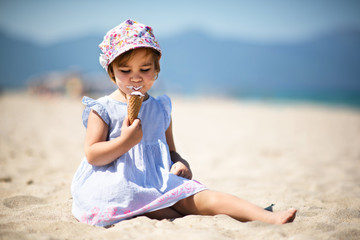 Happy Child Girl Eating Ice Cream at Beach in Summer Season