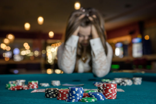 Upset woman in casino sitting behind poker table