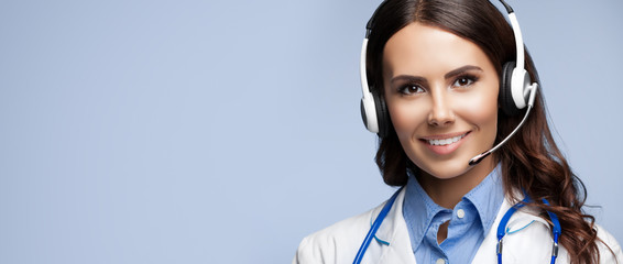 Portrait picture of happy smiling young doctor in headset, with copy space, over grey background