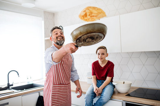 Mature father with small son indoors in kitchen, flipping pancakes.