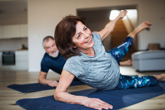 A senior couple indoors at home, doing exercise on the floor.