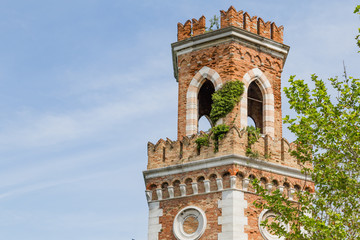 Tower at the entrance of the Arsenale in Vencie Italy, ovegrwon with climbers