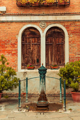 Venice Italy - May 25, 2019:  Anceint venetian water pump on Murano island.