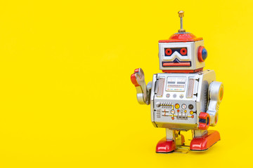 Antique tin toy robot on yellow background. Vintage and classic concept free copy space for text.