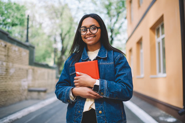 Half length portrait of smiling afro american female student standing with favorite book outdoors in college yard.Attractive hipster girl in stylish spectacles and jeans jacket walking with notepad