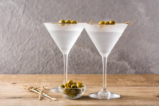 Classic Dry Martini with olives in glass on wooden table